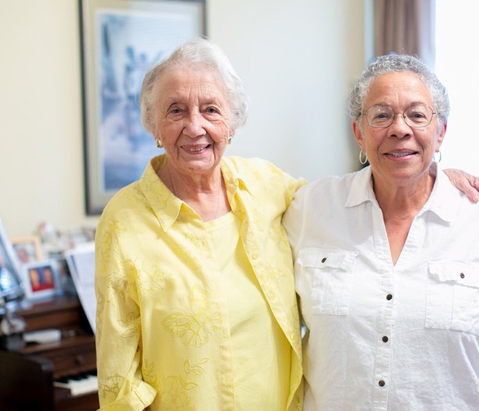 Two older women standing with arms on each others shoulders